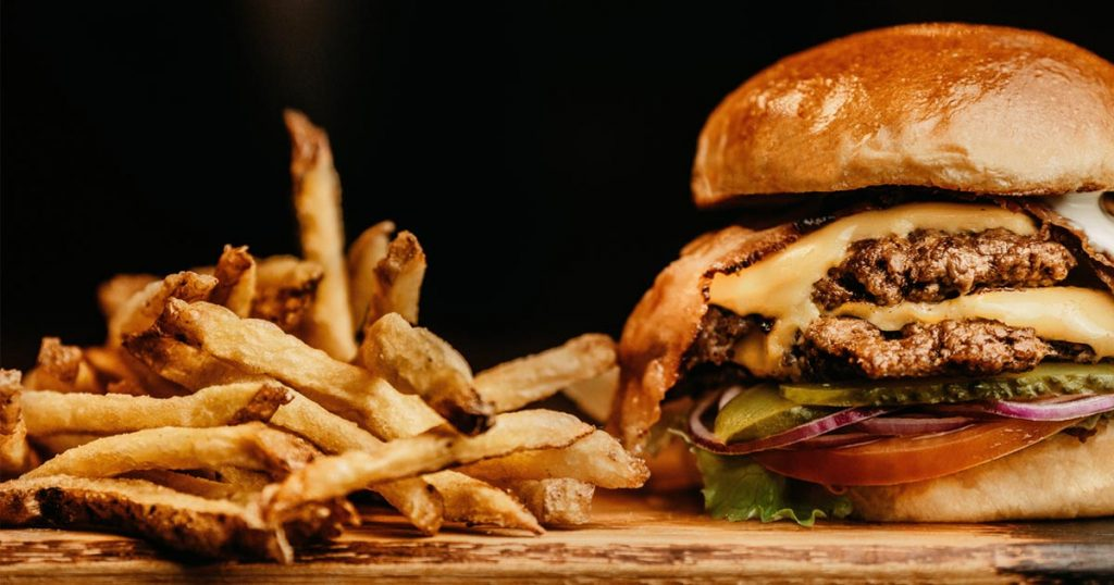 Hamburger mit Rindfleisch auf einem Holzbrett, daneben Pommes Frites.
