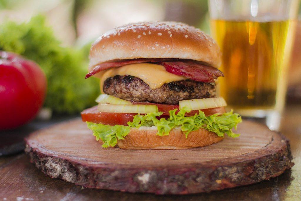 Hamburger mit Bacon auf Holzbrett.