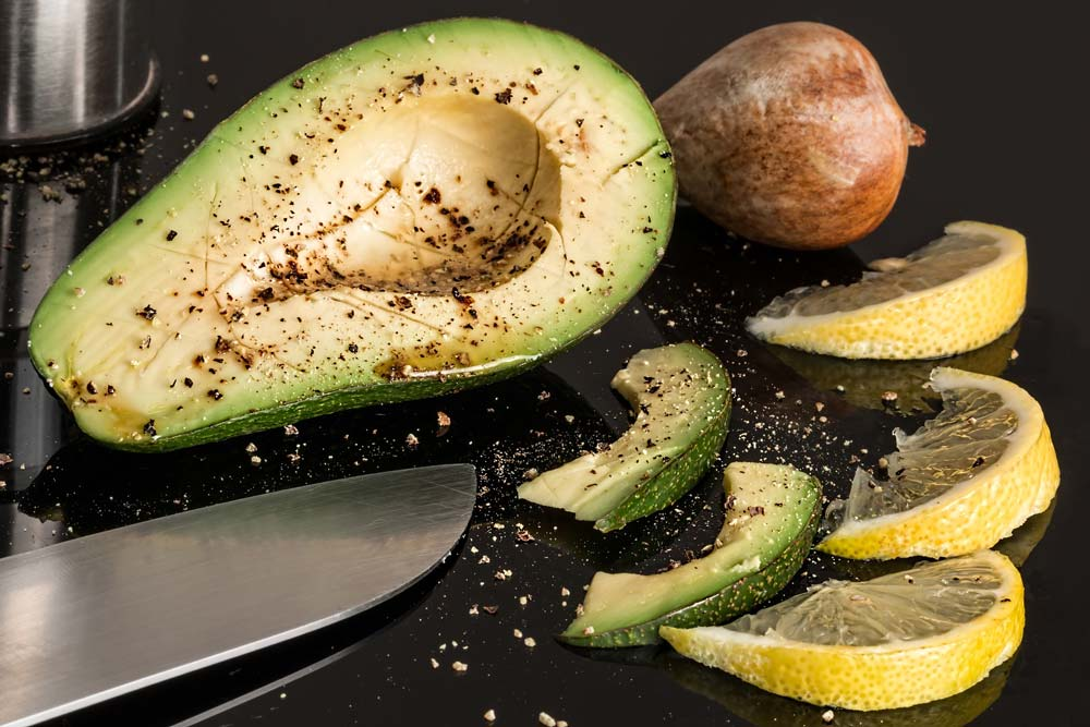 Aufgeschnittene Avocado, daneben Zitrone und ein Messer
