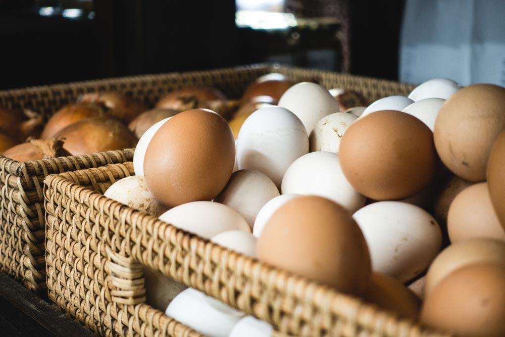 Weiße und braune Eier in einem Korb