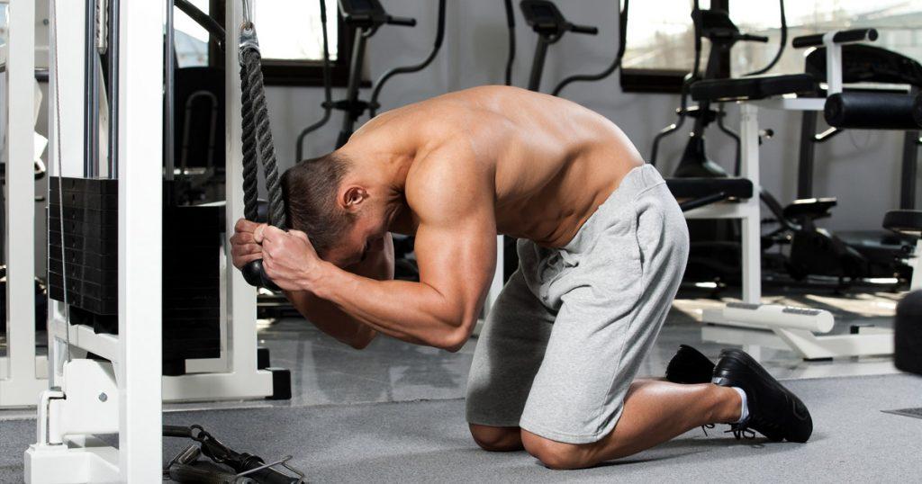 Fitness Athlet führt Sit Ups Alternative Crunches am Seilzug aus.