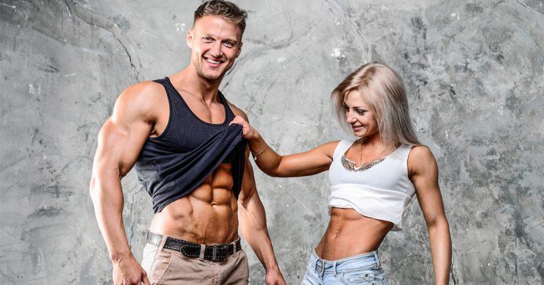Mann und Frau zeigen sich gegenseitig ihren Sixpack.