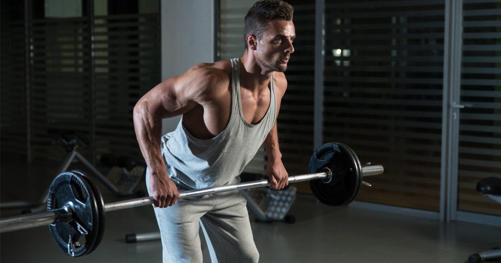 Mann im Fitness-Studio führt Langhantel-Rudern aus.