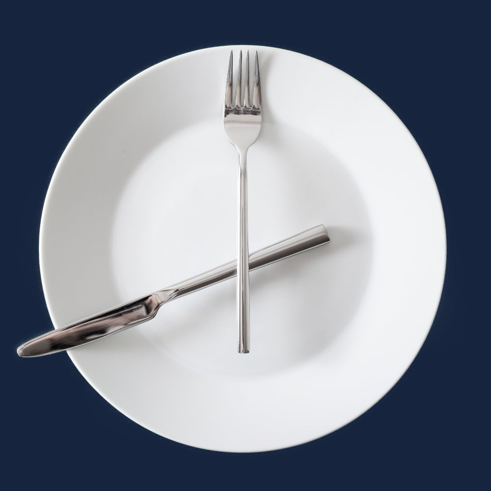 Besteck zu Uhrzeigern angeordnet auf einem weißen Teller