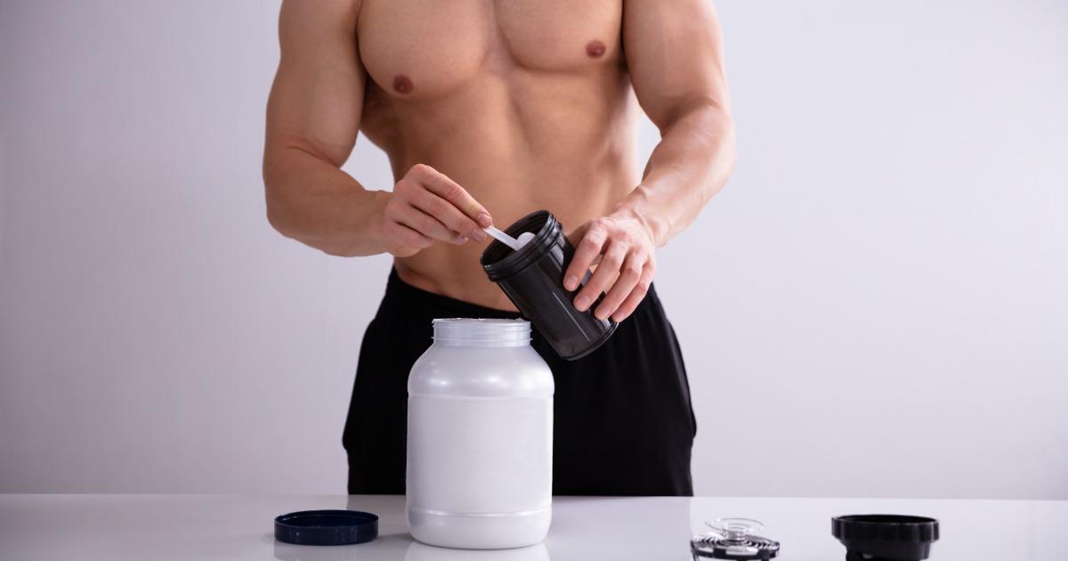 Junger Bodybuilder bereitet sich einen Proteinshake vor