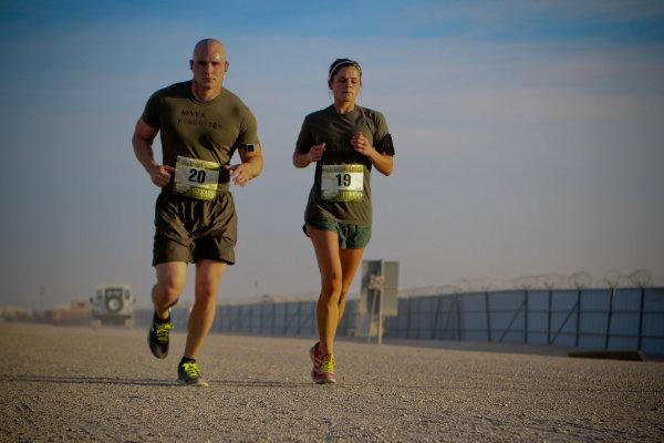 Eine Frau und ein Mann joggen bei mittlerer Intensität auf einer Straße