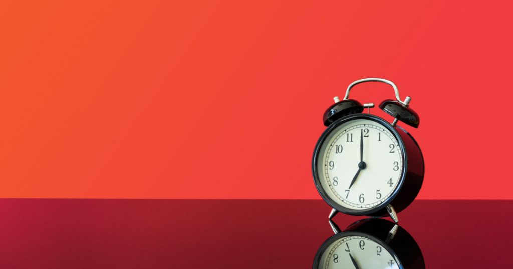 Wecker vor roten Hintergrund