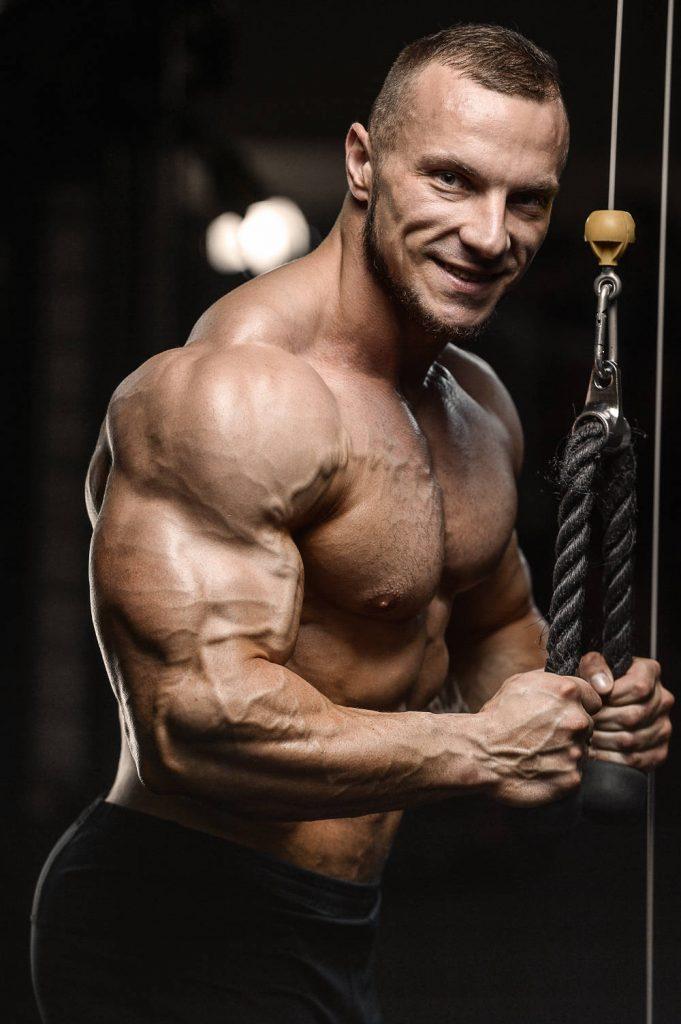 Athletischer Bodybuilding trainiert Trizeps am Kabelzug
