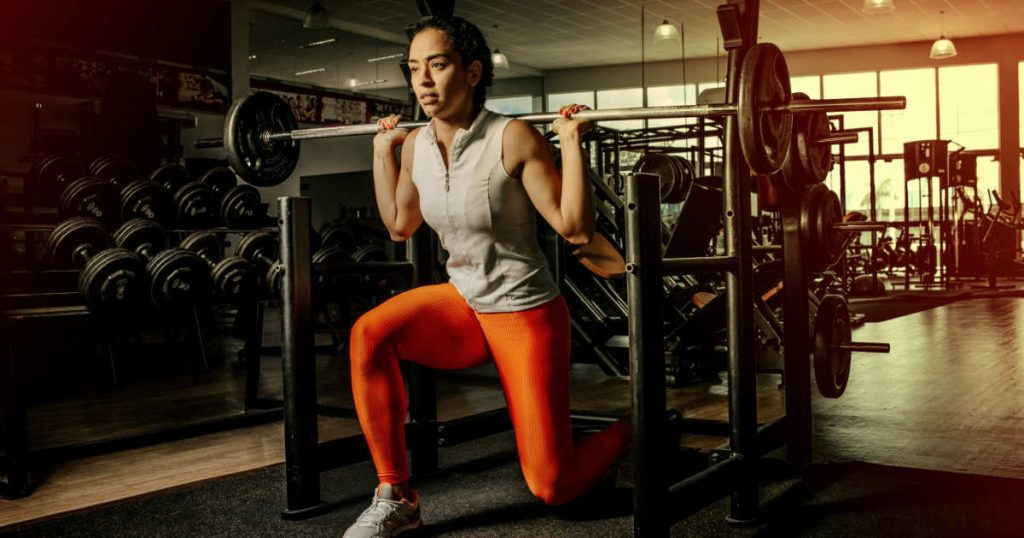 Frau im Fitnessstudio: Ausfallschritte mit Langhantel