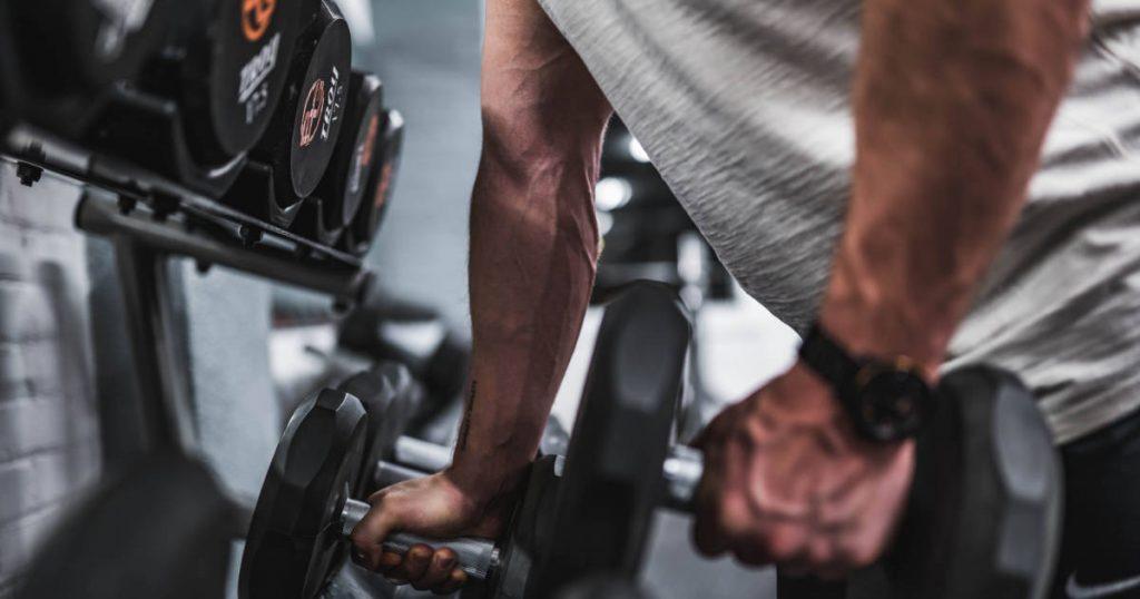 Mann im Fitness-Studio greift nach Kurzhantel