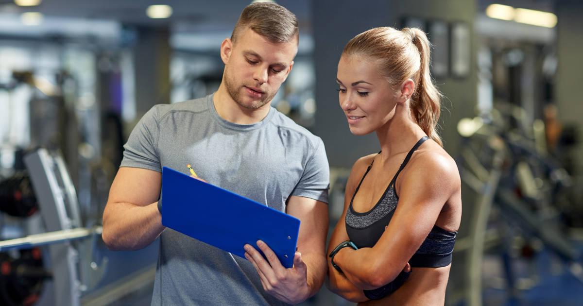 Mann und Frau planen Trainingsfrequenz im Fitnessstudio