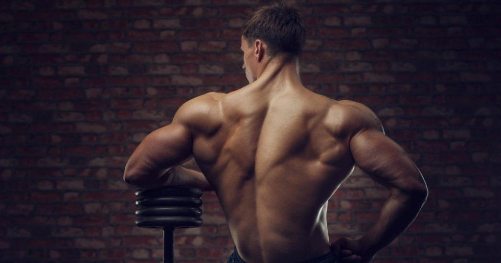 Bodybuilder mit Kurzhantel vor einer Steinwand